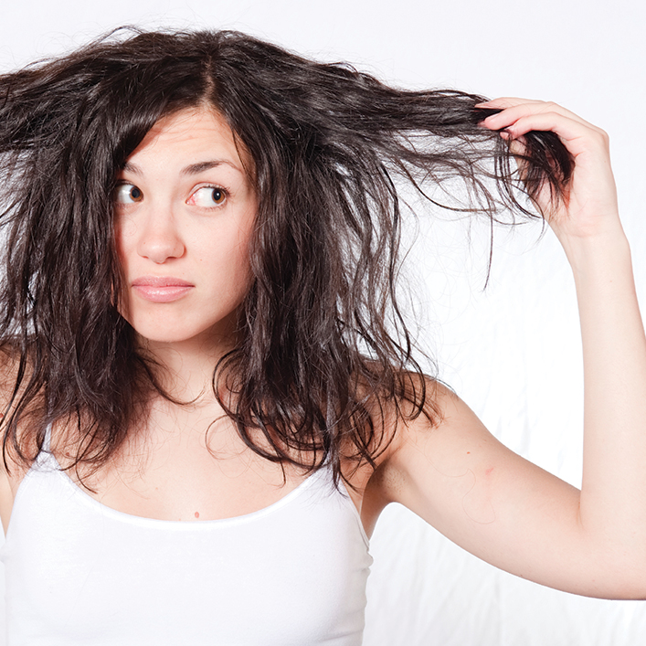 Woman holding out her hair and looking at it with a concerned expression