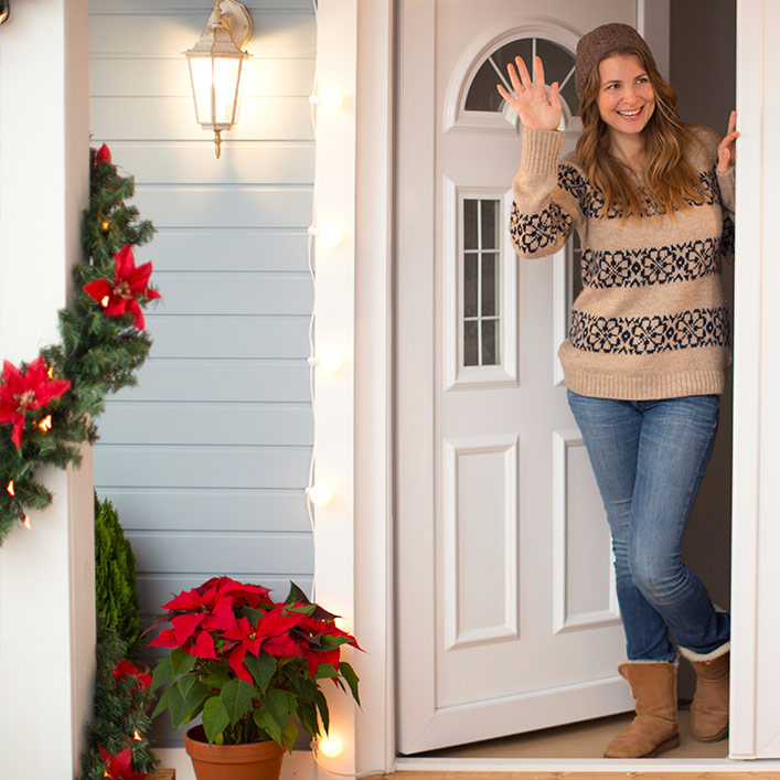 A woman in a sweater waving her hand by an open door to a house