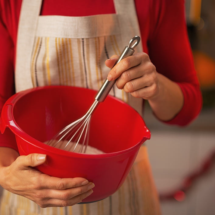 A person mixing baking ingredients in a red bowl