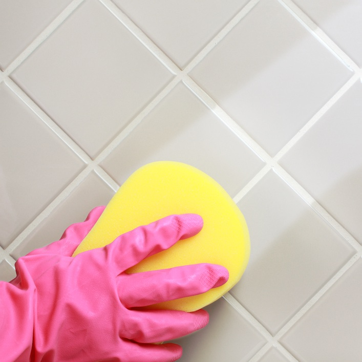A person's gloved hand cleaning the bathroom tiles because of hard water stains