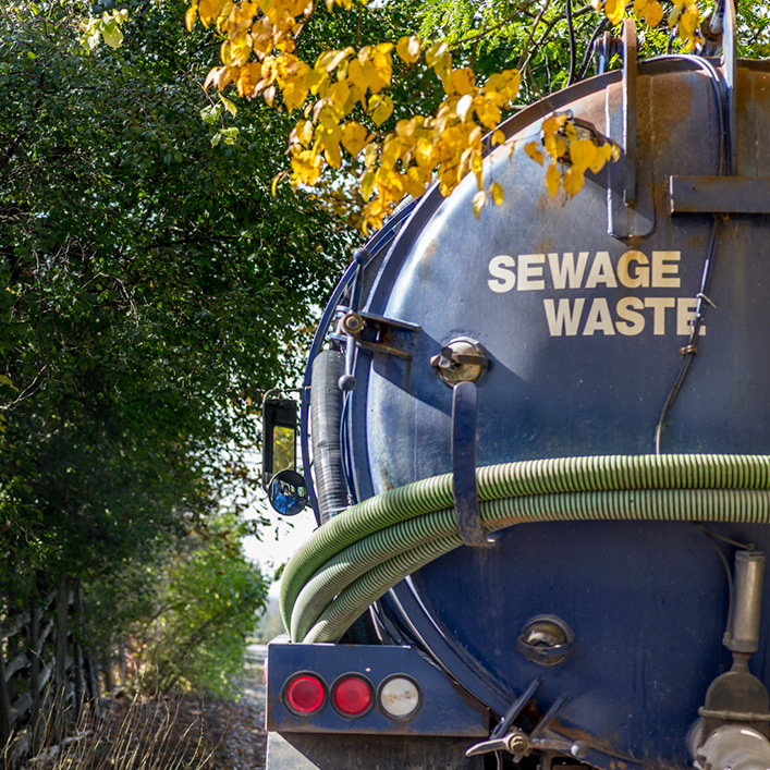 A blue sewage waste truck driving down a road