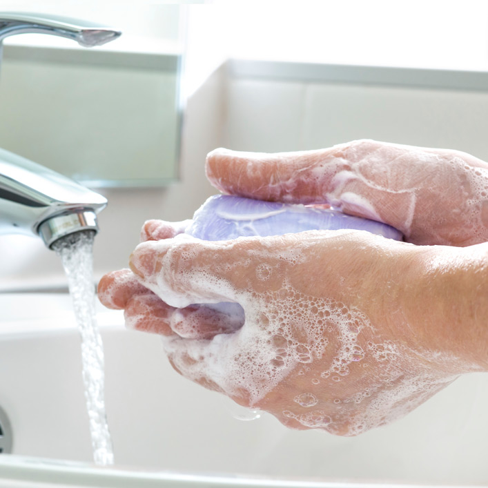 A person washing their hands in a sink with a purple bar of soap