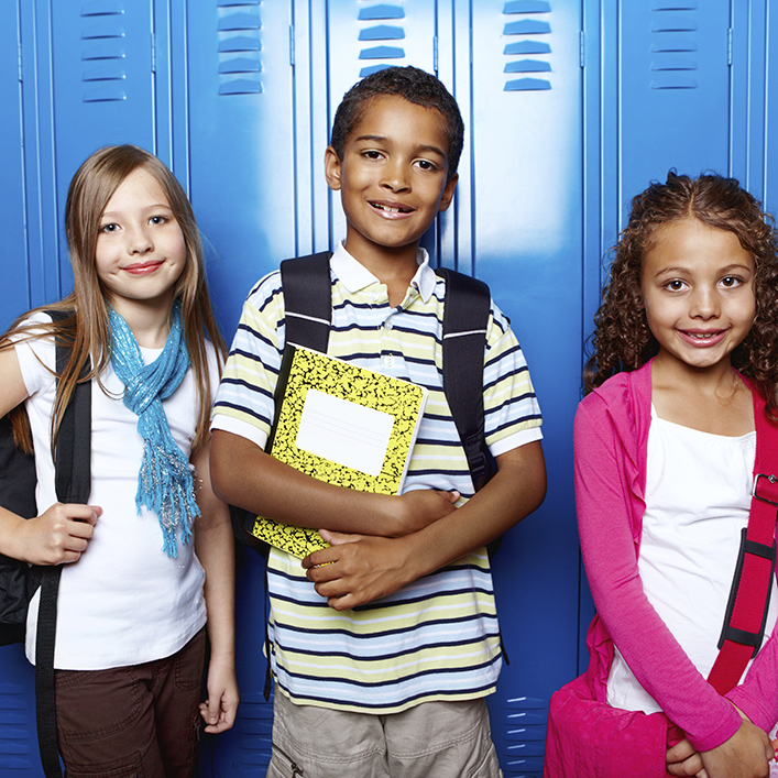 Three kids standing next to each other smiling at the camera in front of blue lockers