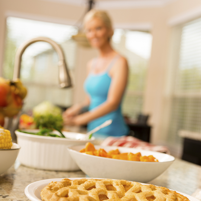 Person baking in a kitchen with a pie in focus in the foreground
