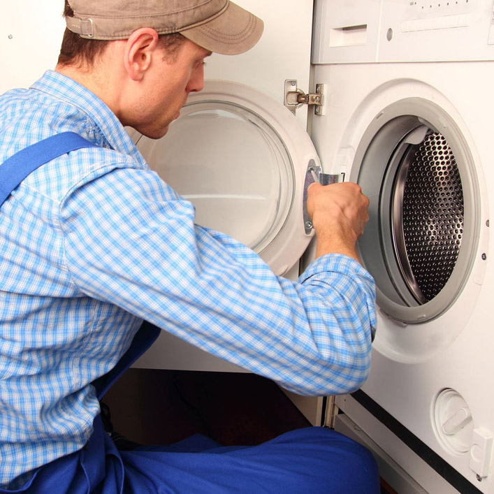 Maintenance person in a blue checkered shirt fixing the door to a washing machine